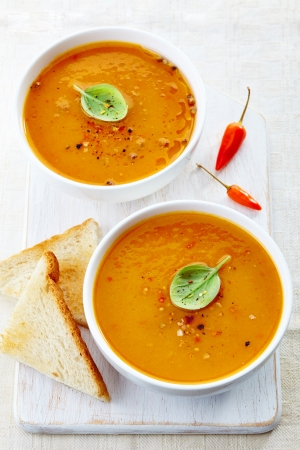 butternut squash: two bowls of squash soup on a white wooden cutting board