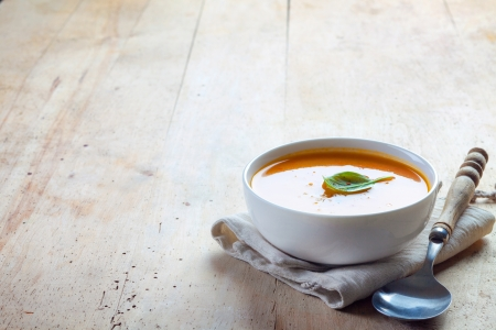 butternut: bowl of squash soup on a wooden table