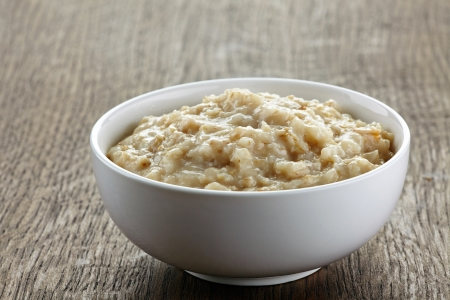Bowl of oats porridge on wooden table
