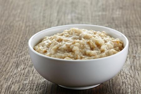 porridge: Bowl of oats porridge on wooden table Stock Photo