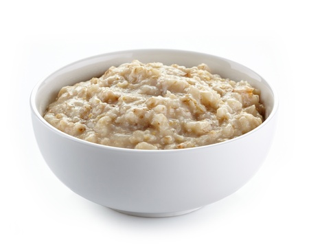 Bowl of oats porridge on a white background Stock Photo