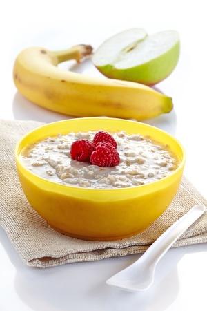 Bowl of oats porridge and fresh fruits Stock Photo