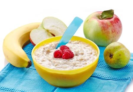comiendo cereal: Tazón de fuente de gachas de avena con frutas frescas. Alimento para bebé
