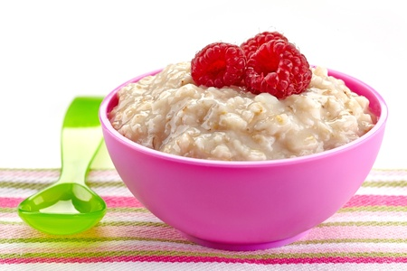 Bowl of oats porridge with fresh berries. Baby food photo