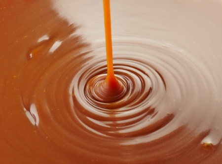 pouring sweet caramel sauce on caramel background Imagens