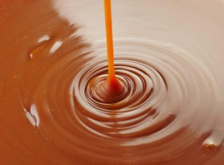caramelo: verter la salsa de caramelo dulce de caramelo de fondo Foto de archivo