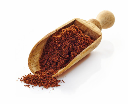 wooden scoop with ground coffee on a white background