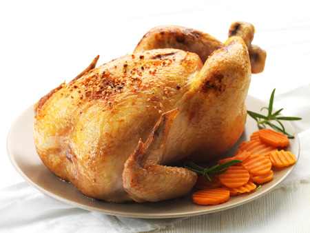 baked chicken: Roast chicken and prepared carrots on plate Stock Photo