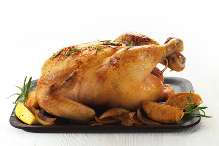 Roast chicken and caramelized onions on wooden plate photo