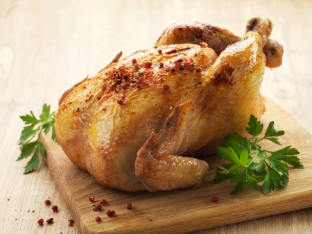 carne de pollo: Pollo asado y perejil en la tabla de cortar de madera
