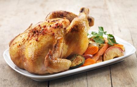 Gebraden kip en diverse groenten op een witte plaat Stockfoto