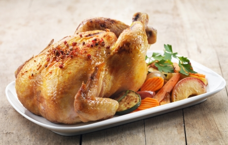 baked chicken: Roast chicken and various vegetables on a white plate Stock Photo