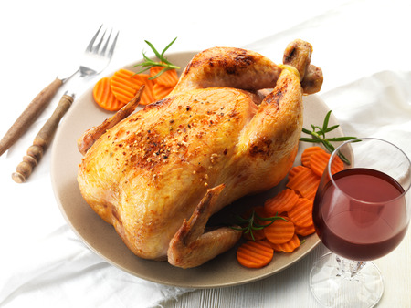 Roast chicken and prepared carrots on plate Stock Photo