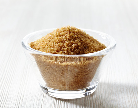raw gold: Cane sugar in a glass bowl on white wooden table Stock Photo