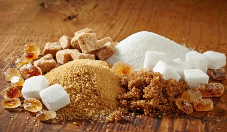 raw gold: various types of sugar on wooden table Stock Photo