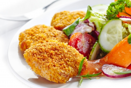 nuggets: chicken nuggets and vegetable salad on a plate Stock Photo
