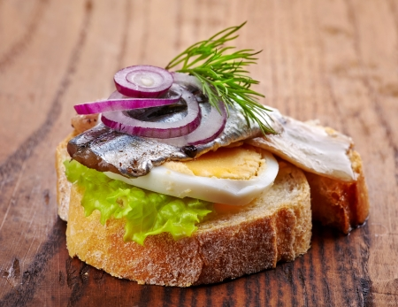 anchovy fish: bread with anchovies decorated with red onion and dill on wooden table
