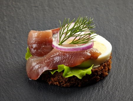 anchovy fish: canape with anchovy and egg on dark background