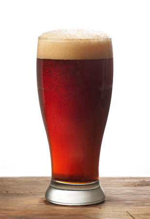 amber light: glass of dark beer on wooden table