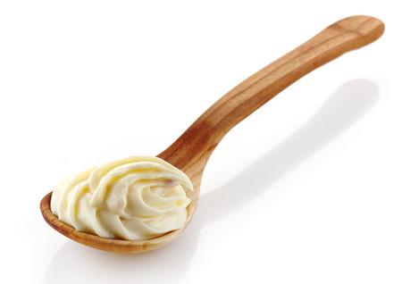 mayonesa: cuchara de madera con crema de queso sobre un fondo blanco