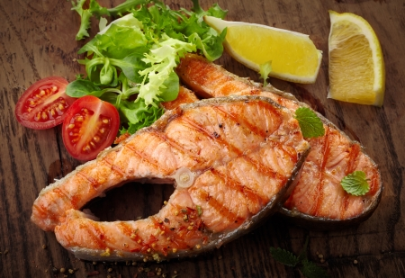grilled salmon: grilled salmon steak slices on wooden cutting board