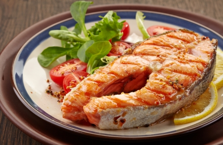 fresh grilled salmon steak slice on a plate photo