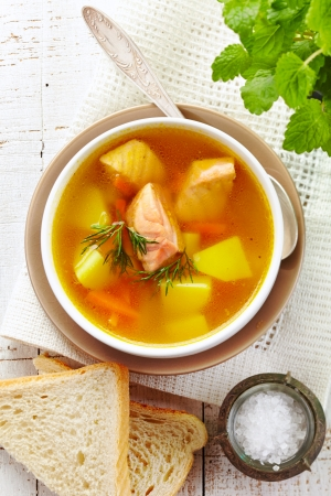 kitchen table top: bowl of fish soup on wooden table
