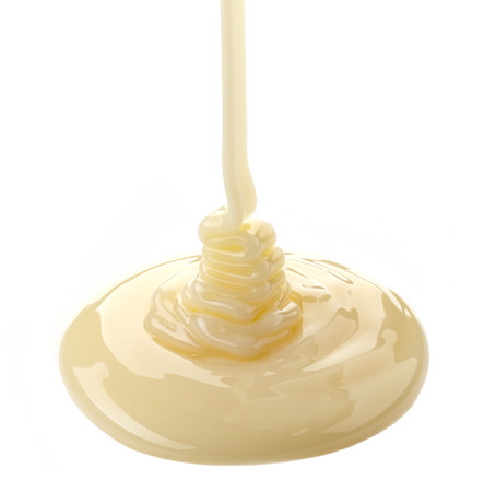 pouring condensed milk on a white  Stock Photo