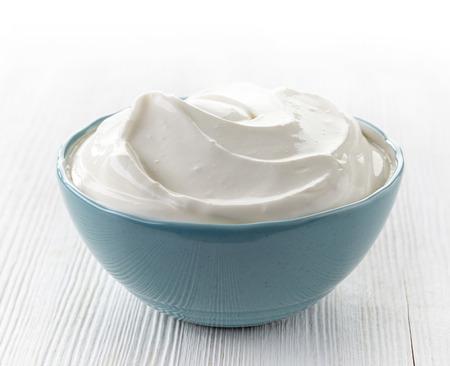 yaourts: bol de crème sure sur table en bois blanc