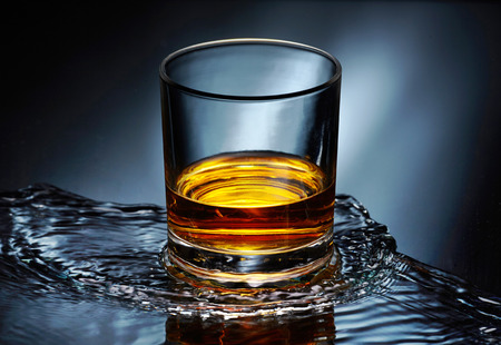 glass of whiskey on water splash background photo