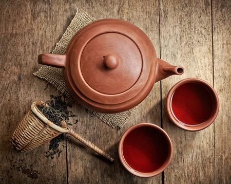 taza de te: tetera y tazas de sobre mesa de madera
