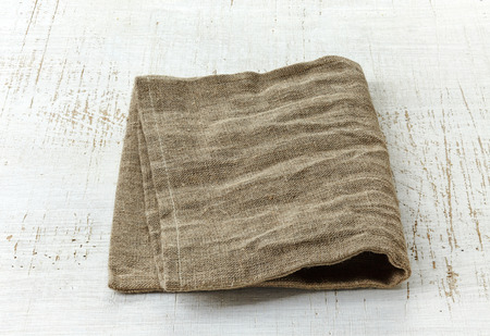 serviette: natural linen napkin on white wooden table