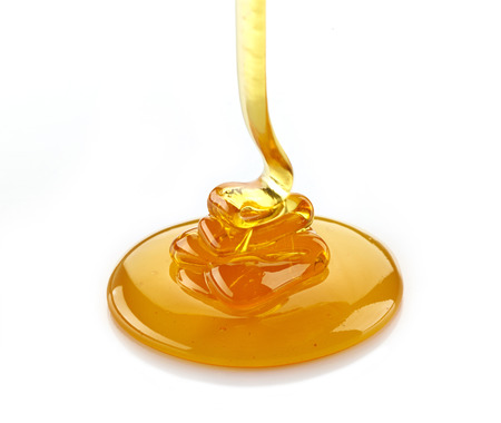 pouring honey on a white background Stock Photo