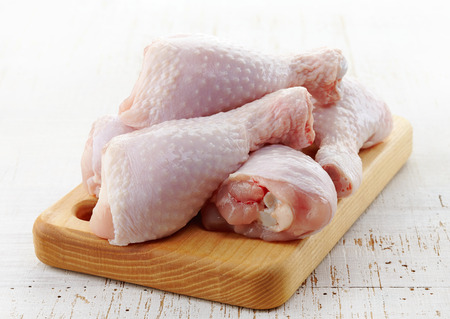 raw chicken legs on wooden cutting board photo