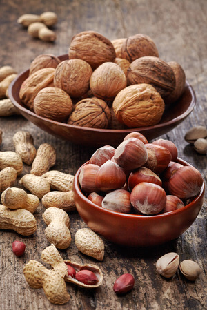 various kinds of nuts on old wooden table photo