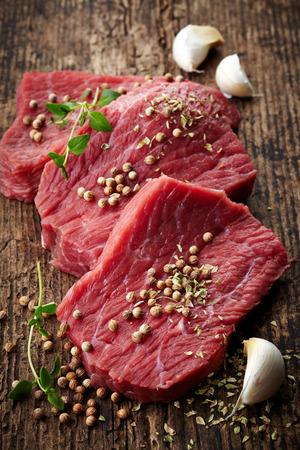 fresh raw meat for steak on wooden cutting board