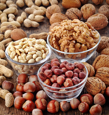 kinds: various kinds of nuts on wooden table Stock Photo