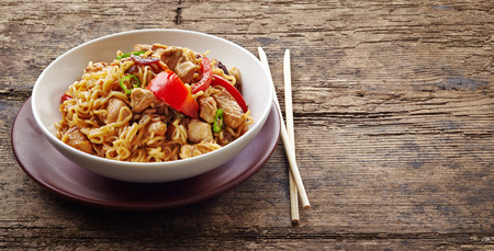 chicken noodle: bowl of noodles with chicken and vegetables on wooden table
