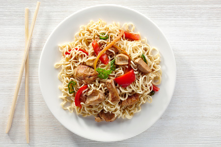 noodles with chicken and vegetables on white plate