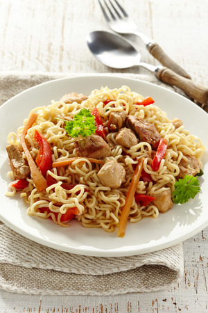 Noodles with chicken and vegetables on white plate photo