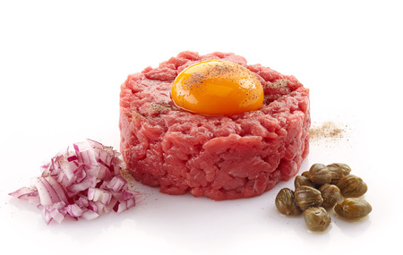 tartar: fresh beef tartare with egg, onions and capers on white background