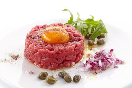 frisches Rindfleisch-Tatar mit Ei auf weißem Teller Standard-Bild