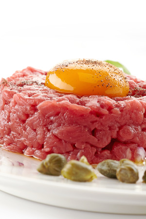 fresh beef tartar with egg on white background