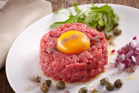 fresh beef tartar with egg on white plate