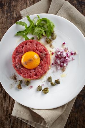 steak tartare: fresh beef tartar with egg on white plate