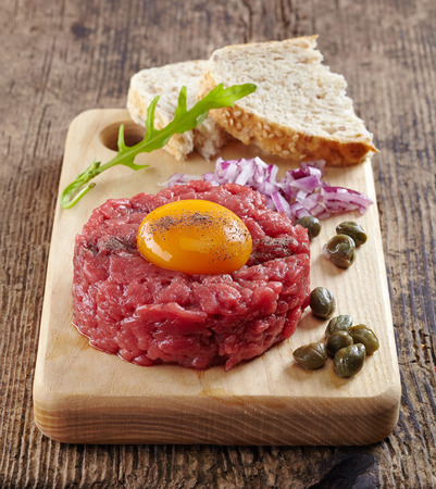 tartar: fresh beef tartar with egg on wooden cutting board