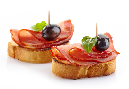 Spanish food tapas, Toast with serrano meat, olive and basil  Stock Photo
