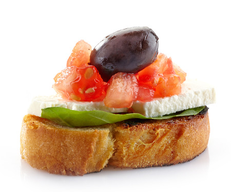 Spanish food tapas, Toast with basil, tomato, fresh cheese and olive photo