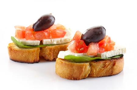 Spanish food tapas, Toast with basil, tomato, fresh cheese and olive photo