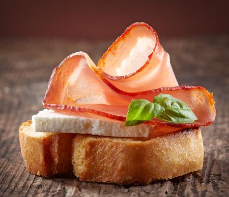 queso de cabra: Tapas de los alimentos españoles pan tostado con queso de cabra y jamón serrano Foto de archivo